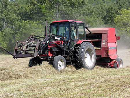 Hay baler sweeping up the wind rows of dried grass